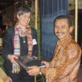 Sandra Niessen presenting Legacy in cloth to Consul General Sinambela of Indonesia on his visit, with his wife, to the San Francisco Tribal and Textile Arts show.