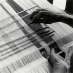 fig. Tech 4.1 A weaver uses the cross in the warp to retain the order of the warp yarns. Silindung Valley. 1980. She counts the yarns at the cross with her left hand and inserts rods with her right. The rods collect the warp yarns that will be ikat-dyed in a similar fashion.